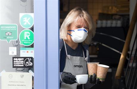 výdejové okénko paní podává kávu